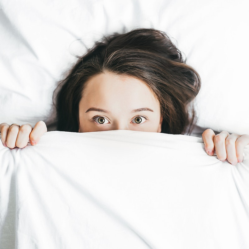 woman hiding half her face under the covers